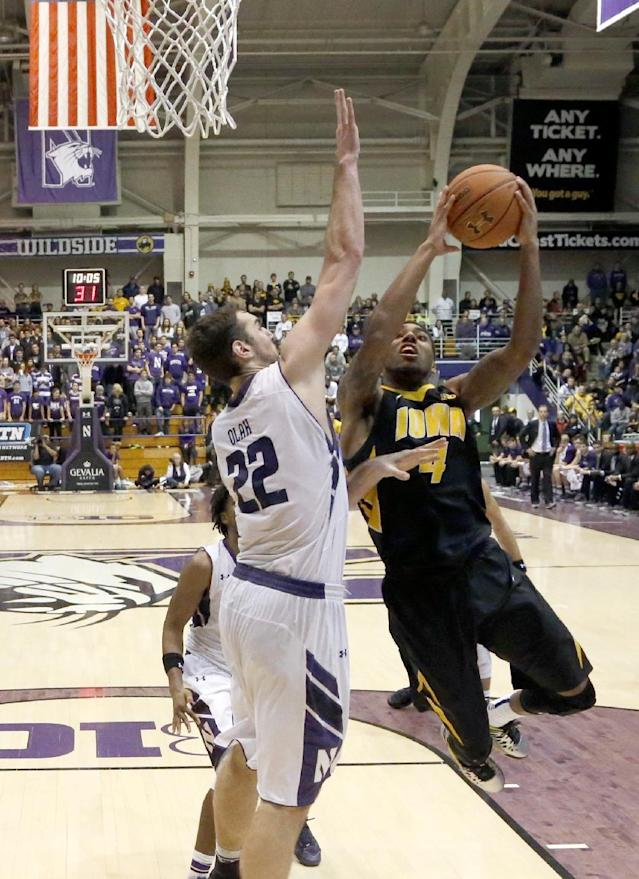 Iowa guard Roy Devyn Marble (4) shoots past Northwestern center Alex Olah during the second half of an NCAA college basketball game Saturday, Jan. 25, 2014, in Evanston, Ill. Iowa won 76-50. (AP Photo/Charles Rex Arbogast)