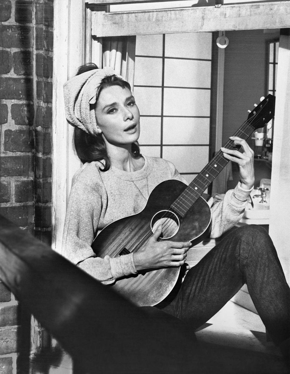 """<p>In one of <em>Breakfast at Tiffany's </em>most memorable scenes, Audrey Hepburn rocks a casual denim look. The actress paired a baggy sweatshirt with dark wash, straight leg jeans and a hair wrap for her """"Moon River"""" serenade.  </p>"""