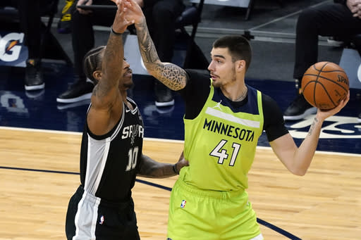 Minnesota Timberwolves' Juancho Hernangomez, right, looks for help as San Antonio Spurs' DeMar DeRozan defends in the first half of an NBA basketball game Saturday, Jan. 9, 2021, in Minneapolis. (AP Photo/Jim Mone)