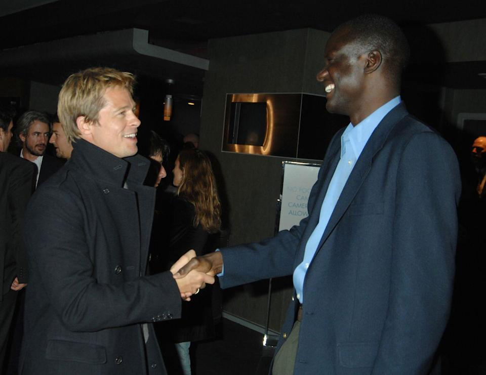 <p>Pitt greets John Bul Dau, one of the stars of his 2007 documentary <em>God Grew Tired of Us</em>. The movie was produced by Pitt's production company, Plan B Entertainment. He started it in 2001 with his then-wife, Aniston, and business partner Brad Grey. But after their divorce, Pitt became the sole owner of the company. </p>
