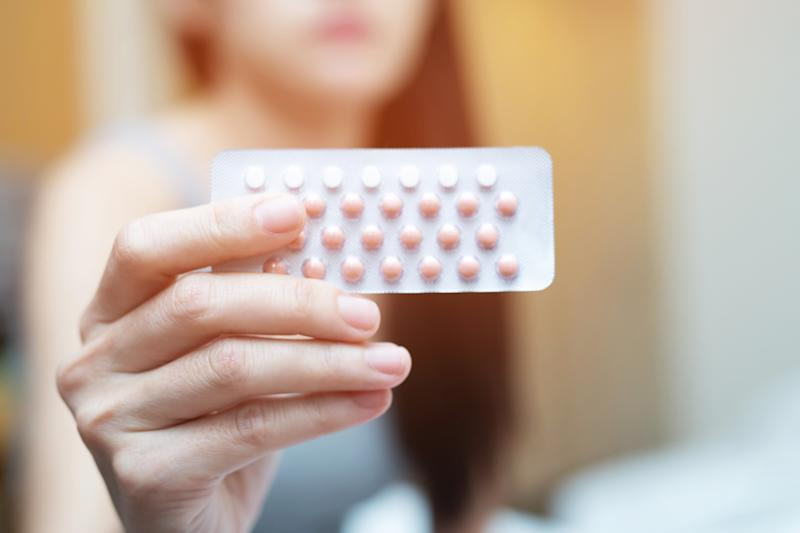 Woman hands opening birth control pills in hand on the bed in the bedroom. Eating Contraceptive Pill.