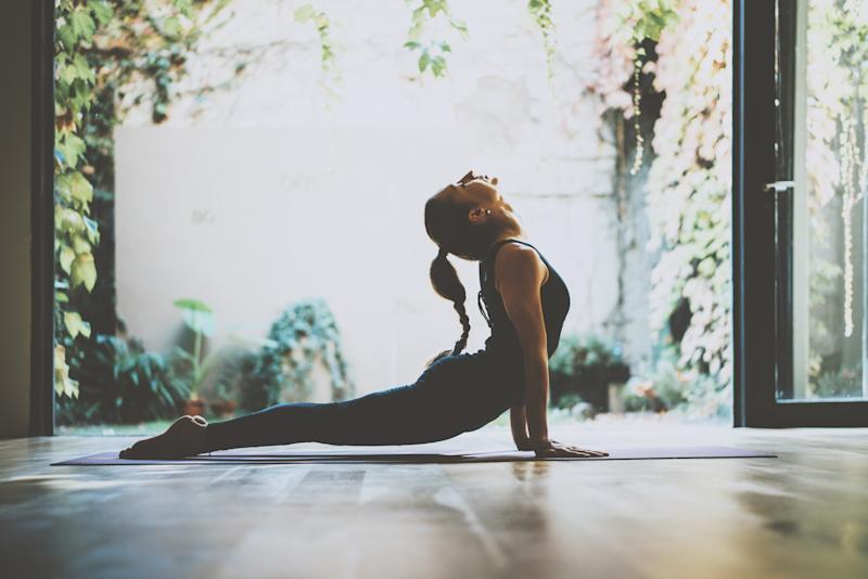 A woman doing yoga in front of French doors open to a courtyard filled with plants