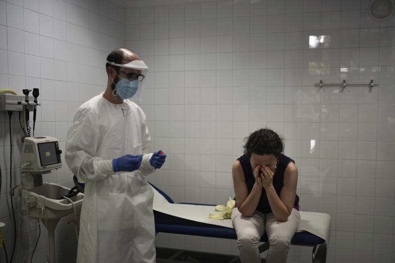 In this July 31, 2020 file photo, Emma Gaya reacts after having a nasal swab during a COVID-19 test at a Primary Health Care Center in Sant Sadurní d'Anoia, Catalonia region, Spain. Like most Spaniards, Gaya thought the worst of the pandemic was behind her. She came in because she had a fever, one of the typical symptoms of COVID-19. (AP Photo/Felipe Dana)