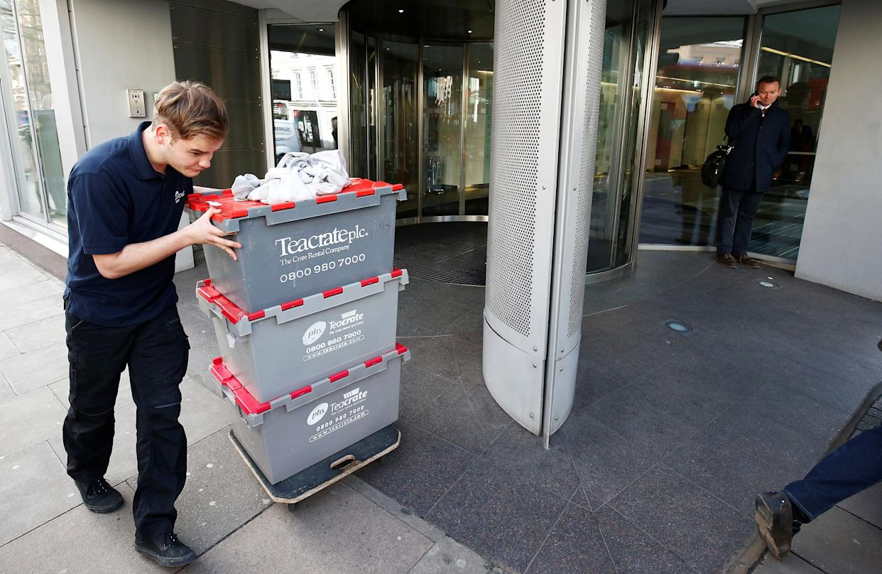A man wheels storage crates from the building that houses the offices of Cambridge Analytica in central London, Britain, on Tuesday. (Photo: Henry Nicholls / Reuters)