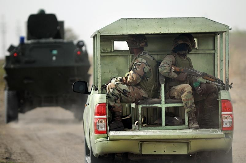 Nigerian soldiers patrol in the north of Borno state close to a Boko Haram former camp on June 5, 2013 near Maiduguri (AFP Photo/Quentin Leboucher)