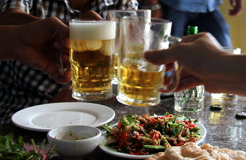 Diners enjoy a dish of cat meat while drinking beer at a restaurant in Hanoi on June 19, 2014 (AFP Photo/)