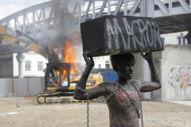 "<p>A chained activist, with his body painted in black, lifts a fake stone bearing the name of French President Emmanuel Macron and the word ""people"" on his torso as he poses for photographers while a digger set ablaze by demonstrators is seen on background during the traditional May Day rally in the center of Paris, France, Tuesday, May 1, 2018. Each year, people around the world take to the streets to mark International Workers' Day, or May Day. (Photo: Francois Mori/AP) </p>"