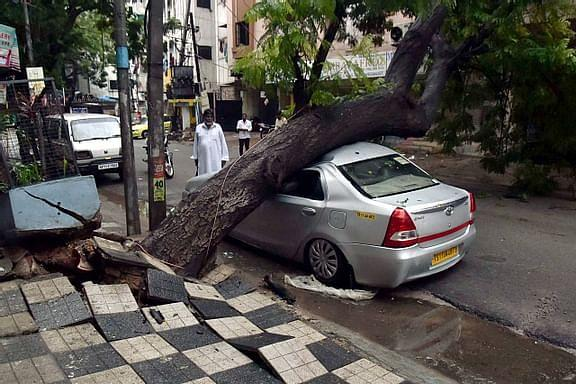A car lies buried under an uprooted tree after heavy rain, at Noor Khan Bazar in Hyderabad, Wednesday, Oct. 14, 2020.