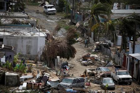 FILE PHOTO: A man carrying a water container walks next to damaged houses after the area was hit by Hurricane Maria in Canovanas