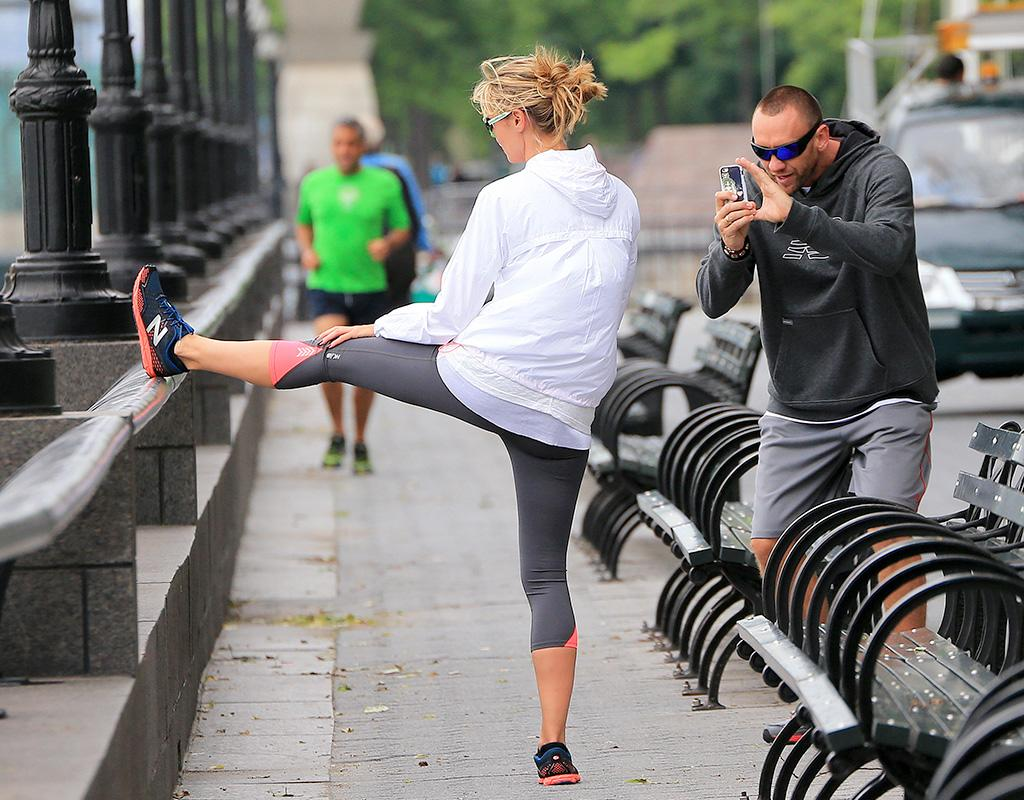 Heidi Klum stretches while Martin Kristen takes a photo at a park in NYC.