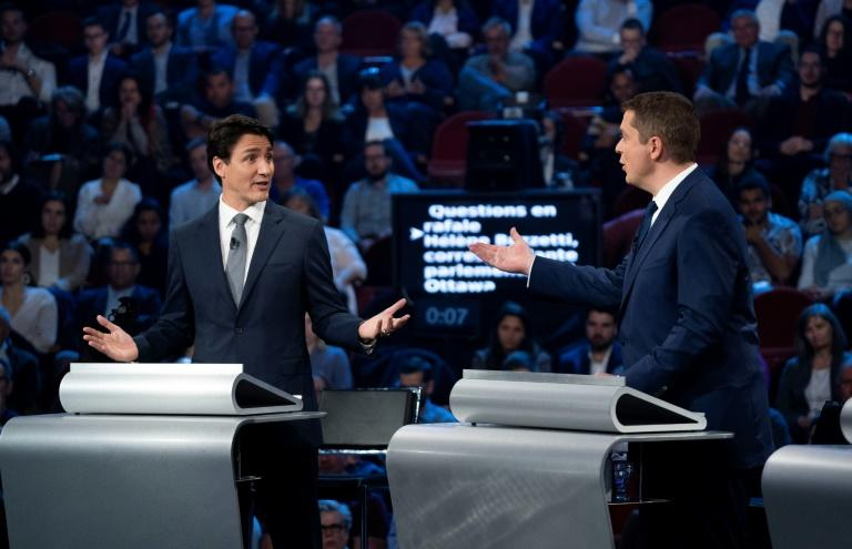 Canada's Prime Minister and Liberal leader Justin Trudeau (L) and Conservative leader Andrew Scheer, pictured during a debate, are in a dead heat on the eve of national elections (AFP Photo/Chris Wattie)