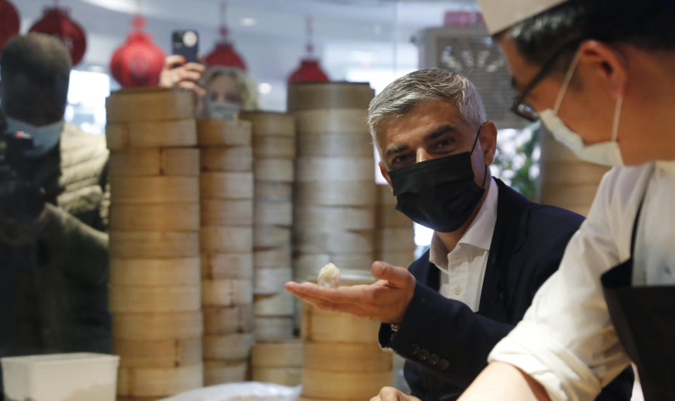 Mayor of London Sadiq Khan, second right attempts to prepare dumplings with head chef Ling Bing, during a visit to Dumplings Legend in China Town central London, Monday, May 17, 2021. Pubs and restaurants across much of the U.K. are opening for indoor service for the first time since early January even as the prime minister urged people to be cautious amid the spread of a more contagious COVID-19 variant. (AP Photo/Alastair Grant)