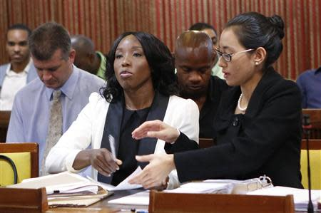 Jamaica's Olympic sprinter Sherone Simpson (front L), who tested positive for doping at the Jamaican Championships in 2013, sits with her attorney Dianne Chai (front R) as they wait for the beginning of the hearing before the country's anti-doping commission in Kingston January 7, 2014. REUTERS/Gilbert Bellamy