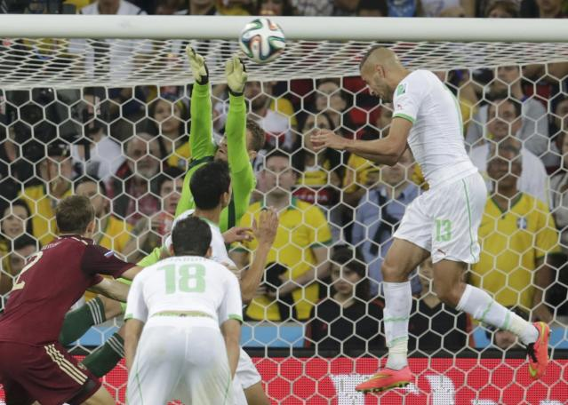 Algeria's Islam Slimani (R) heads the ball to score a goal against Russia during their 2014 World Cup Group H soccer match at the Baixada arena in Curitiba June 26, 2014. REUTERS/Henry Romero (BRAZIL - Tags: SOCCER SPORT WORLD CUP)
