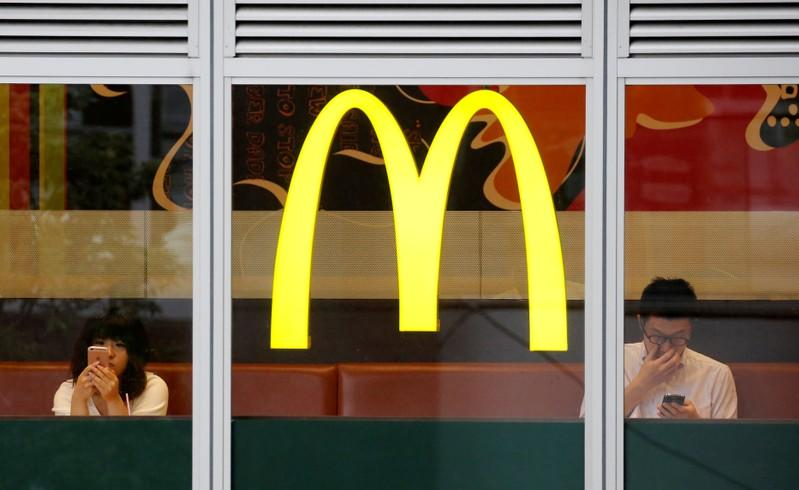 Customers using mobile phones, are seen through the windows of a McDonald's store in Tokyo