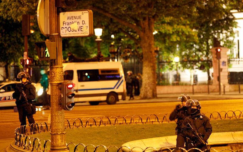 Police officers take positions near the Champs Elysees avenue in Paris, France, after a fatal shooting in which a police officer was killed along with an attacker - Credit: AP