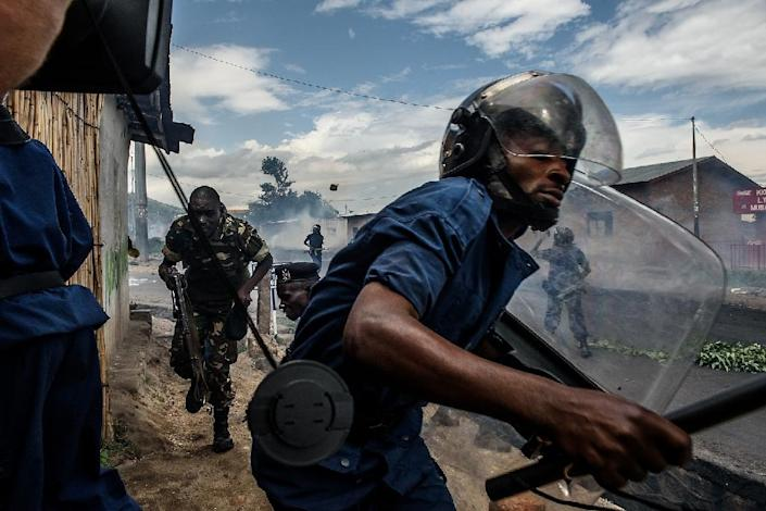 Burundi's police and armed forces run after protesters throwing stones on May 13, 2015 in Bujumbura (AFP Photo/Jennifer Huxta)