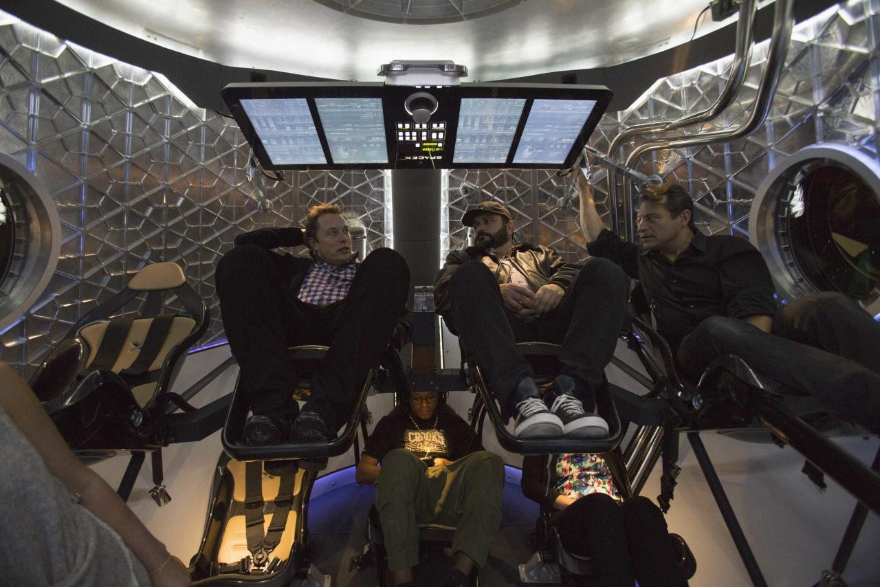 SpaceX CEO Elon Musk (L) sits with guests inside the Dragon V2 spacecraft after it was unveiled in Hawthorne, California May 29, 2014. Space Exploration Technologies, or SpaceX, on Thursday unveiled an upgraded passenger version of the Dragon cargo ship NASA buys for resupply runs to the International Space Station. REUTERS/Mario Anzuoni (UNITED STATES - Tags: POLITICS TRANSPORT SCIENCE TECHNOLOGY SOCIETY)