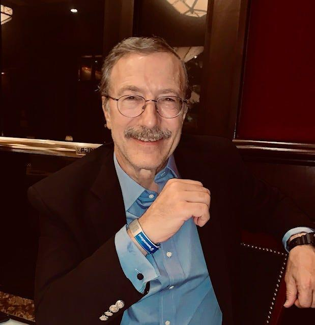 Dr. Tashof Bernton shows off his ImmunaBand, a $20 wristband he created that features a QR code link to the wearer's official vaccination records.