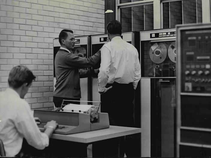 "Computer at the Sydney Technical College.Charlie Shuetrim (lecturer) with pupil Ken Robson (right).Instructor Charles Shuetrim, explains the workings of the IBM 1401 computer to students at Sydney Technical College. Student in foreground is punching out a ""program"" to be fed into the machine. August 2, 1966."