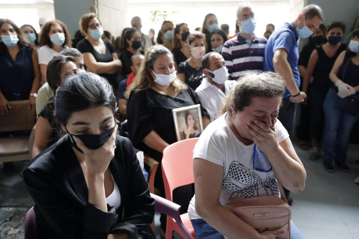 Families, friends and colleagues of four nurses of the Saint George Hospital University Medical Center, who died in the Tuesday explosion at the seaport of Beirut, attend a mass officiated by Greek Orthodox Metropolitan of the Archdiocese of Beirut, Elias Audi, in Beirut, Lebanon, Thursday, Aug. 6, 2020. (AP Photo/Hassan Ammar)