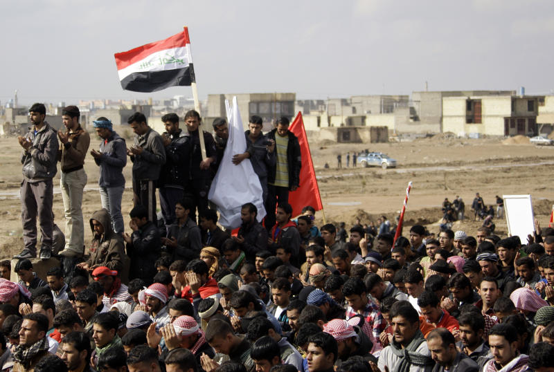 Iraqis gather for Muslim noon prayers, the highlight of the religious week, as they hold national flags during a protest in Fallujah, 40 miles (65 kilometers) west of Baghdad, Iraq, Friday, Feb. 1, 2013. Tens of thousands of Sunni protesters blocked a major highway in western Iraq on Friday, as an al-Qaida-affiliated group called on Sunnis to take up arms against the Shiite-led government. (AP Photo/ Khalid Mohammed)