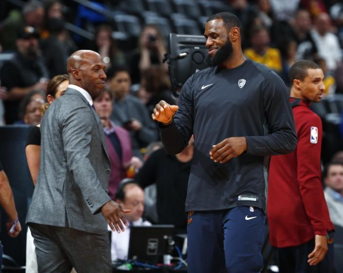 Cleveland Cavaliers forward LeBron James, right, greets television announcer and retired NBA player Chauncey Billups.