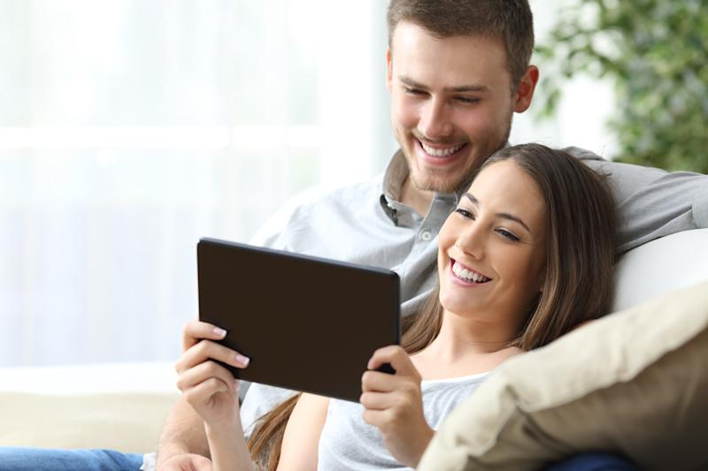A young man and woman smiling while sitting on a couch looking at a tablet.
