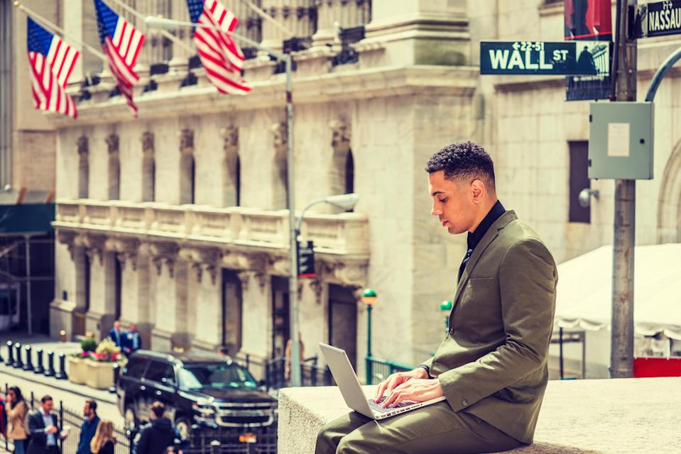 "Young American Businessman traveling, working in New York, wearing green suit, sitting on Wall Street outside vintage office building with American flags, working on laptop computer. Filtered effect""n"