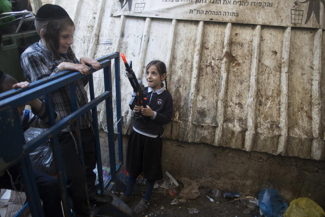 <p>An ultra-Orthodox Jewish girl holds a toy gun during the Kapparot ceremony on Sept. 27, 2017 in Jerusalem, Israel. It is believed that the Jewish ritual, which involves swinging a live chicken above one's head, transfers the sins of the past year to the chicken, which is then slaughtered and traditionally given to the poor. It is performed before the Day of Atonement, or Yom Kippur, the most important day in the Jewish calendar, which this year will start on sunset on Sept. 29. (Photo: Lior Mizrahi/Getty Images) </p>
