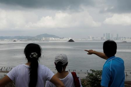 FILE PHOTO: A tourist points China's Xiamen from a former military fort, ahead of the 60th anniversary of Second Taiwan Straits Crisis against China, on Lieyu island, Kinmen county