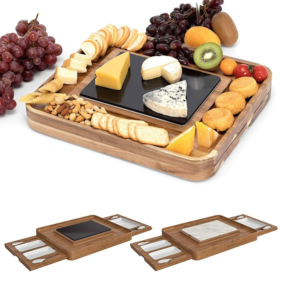 """<p>This acacia wood cheese board does it all, with a reversible marble insert, multiple containers and tools that stow away to fit in any cabinet space.</p> <p><em>Acacia Cheese Board Platter with 2 Slide-Out Drawers, $60 at <a href=""""https://www.amazon.com/Shanik-Bamboo-Cheese-Stainless-Cutlery/dp/B07GFVK13N/ref=as_li_ss_tl?ie=UTF8&linkCode=ll1&tag=fwgiftspartyhostsmsoll1019-20&linkId=3bb83486b848ed3b5abdb0c6d203eaf2&language=en_US"""" target=""""_blank"""">amazon.com</a></em></p>"""
