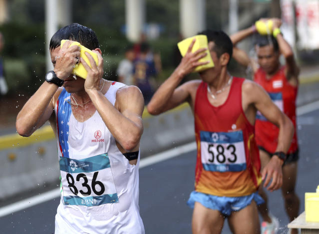 Uzbekistan's Andrey Namkhet sponges himself down with water during the men's marathon at the 18th Asian Games in Jakarta, Indonesia, Saturday, Aug. 25, 2018. (AP Photo/Dita Alangkara)