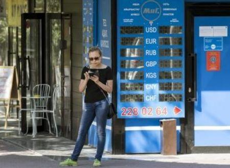 Woman uses her mobile phone next to currency exchange office in Almaty