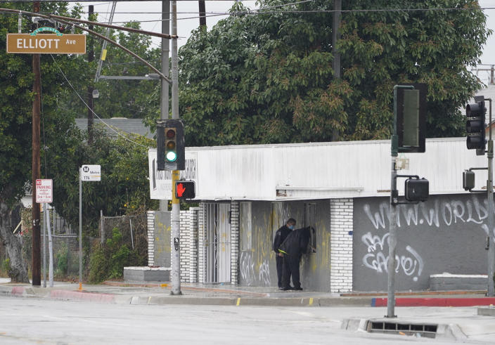 El Monte Police Chief David Reynoso, left, with another officer peeks inside the church's windows after an explosion in El Monte, Calif., Saturday, Jan. 23, 2021. The FBI and local police are investigating an explosion at the Los Angeles-area church that had been the target of protests for its anti-LGTBQ message. (AP Photo/Damian Dovarganes)