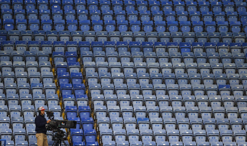 FILE - In this Tuesday, July 14, 2020 file photo, a television cameramen films in front of the empty stands during the English Premier League soccer match between Chelsea and Norwich City at Stamford Bridge in London, England. Spectators will be allowed back into some sports events in England from next week as coronavirus prevention measures are tested ahead of a planned wider reopening of stadiums in October. Domestic cricket on July 26-27 is due to be the first sport since March that fans are allowed to watch in person. (Julian Finney/Pool photo via AP, file)