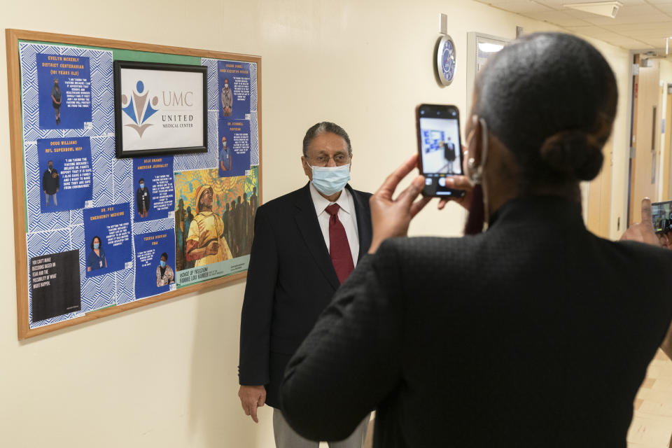 In this Wednesday, Feb. 10, 2021, photo Wallace Charles Smith, 72, who is a pastor at Shiloh Baptist Church, has his picture taken, by United Medical Center's Vice President of Public Relations Toya Carmichael, at the hospital in southeast Washington. The hospital has a board of quotes and photographs from people who have been vaccinated against COVID-19 to encourage others to receive the vaccine. (AP Photo/Jacquelyn Martin)