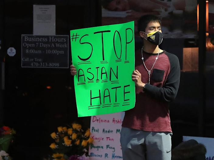 Jesus Estrella, of Kennesaw, Ga., stands outside Youngs Asian Massage on Wednesday, March 17, 2021, in Acworth, Ga., where four people were fatally shot Tuesday.
