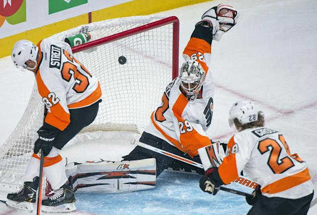 Philadelphia Flyers goaltender Ray Emery, center, is scored on by Montreal Canadiens' Brian Gionta as Flyers' Mark Streit, left, and Claude Giroux defend during the first period of an NHL hockey game in Montreal, Saturday, Oct. 5, 2013. (AP Photo/The Canadian Press, Graham Hughes)