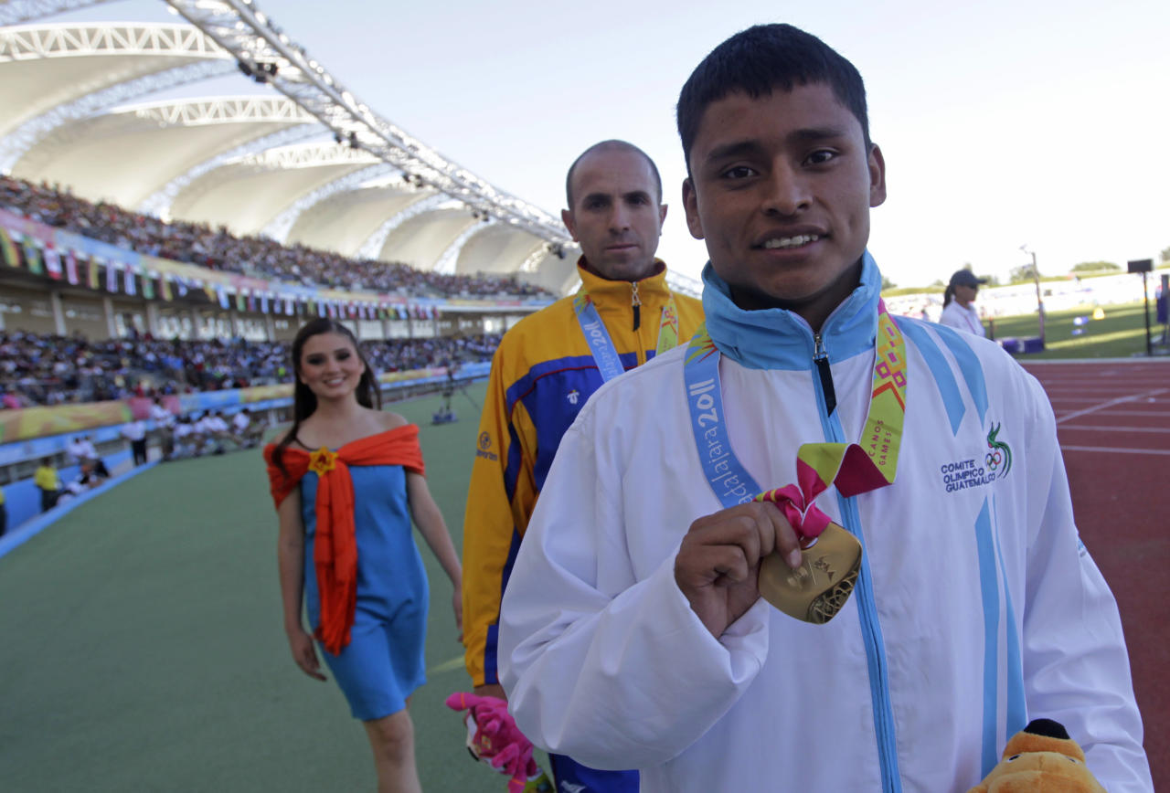 Guatemala's Erick Barrondo, front, walks as he poses with his gold medal after the men's race walk medal ceremony at the Pan American Games in Guadalajara, Mexico, Monday, Oct. 24, 2011. (AP Photo/Silvia Izquierdo)