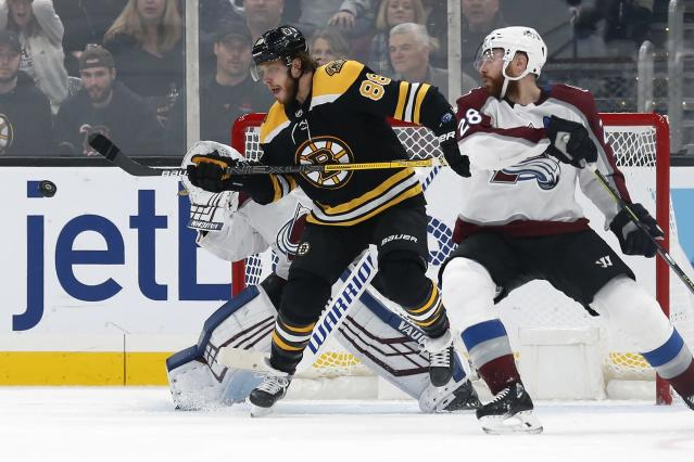 Boston Bruins' David Pastrnak (88) tries to deflect a shot past Colorado Avalanche goalie Pavel Francouz, behind, as Ian Cole (28) defends during the third period of an NHL hockey game in Boston, Saturday, Dec. 7, 2019. (AP Photo/Michael Dwyer)