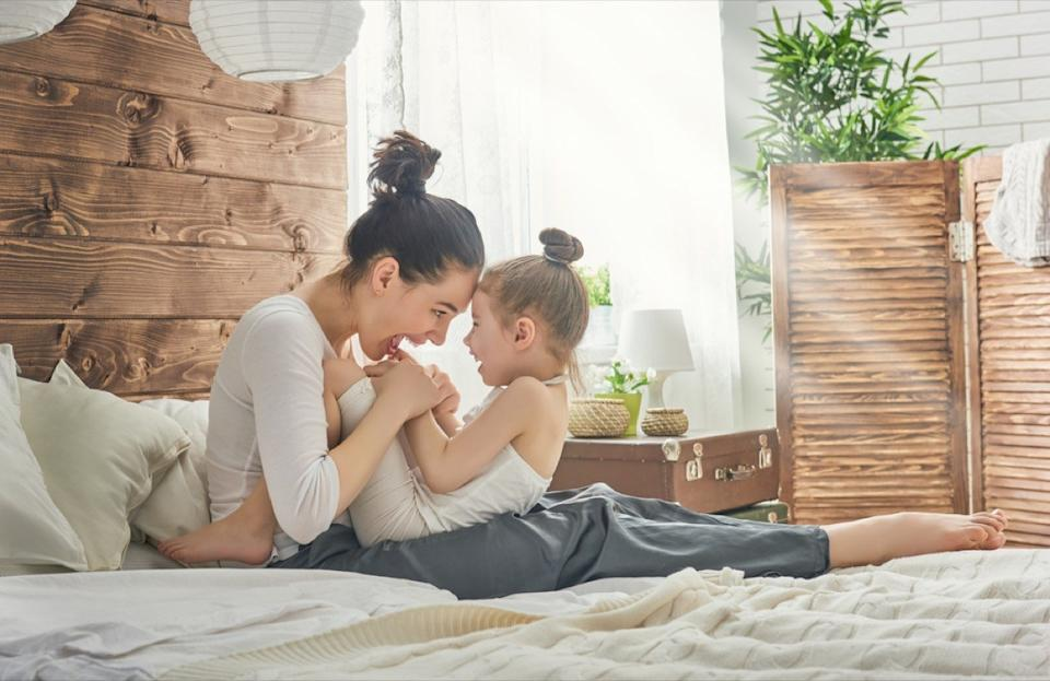 happy mother with child in bed, parenting myths