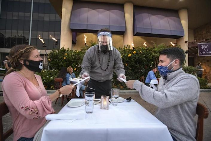 WOODLAND HILLS, CA -JULY 17, 2020: Jason Ruckart, center, a managing partner at Roy's Restaurant in Woodland Hills, hands chopsticks to customers Nicole Lehning, and her husband Kyle, as they dine outdoors. The Lehning's, visiting from Seattle, Washington, said they are on their honeymoon. Fleming's Prime Steakhouse and Roy's Restaurant, located next to each other, converted the valet parking area into outdoor dining. Due to the coronavirus, the restaurants are only allowed to have outdoor dining and takeout as a safety precaution. Valet parking is also not allowed, only self-parking. (Mel Melcon / Los Angeles Times)