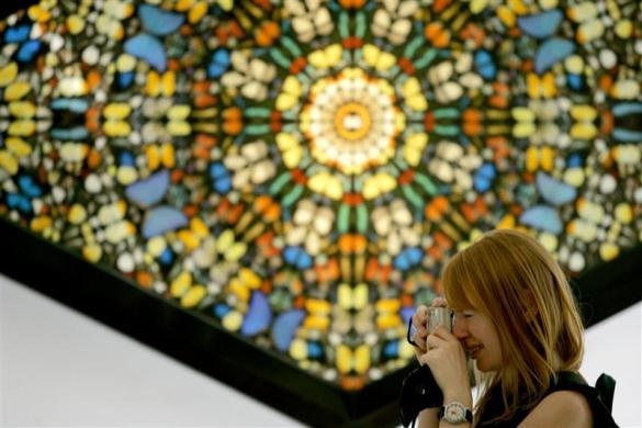 "A visitor to the Hilario Galguera gallery in Mexico City takes a photo as she stands in front of a piece by Damien Hirst titled ""Faithless"" consisting of butterfly wings on canvas and household gloss February 23, 2006."