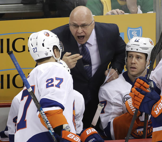 New York Islanders head coach Barry Trotz, center, gives instructions to Anders Lee (27) during the third period in Game 3 of an NHL first-round hockey playoff series against the Pittsburgh Penguins in Pittsburgh, Sunday, April 14, 2019. The Islanders won 4-1. (AP Photo/Gene J. Puskar)