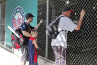 FILE - In this March 12, 2020, file photo, baseball fans look through a fence at Hammond Stadium after a game between the Minnesota Twins and the Baltimore Orioles was canceled, in Fort Myers, Fla. On MLBs opening day, ballparks will be empty with the start of the season on hold because of the coronavirus pandemic. (AP Photo/Elise Amendola, File)