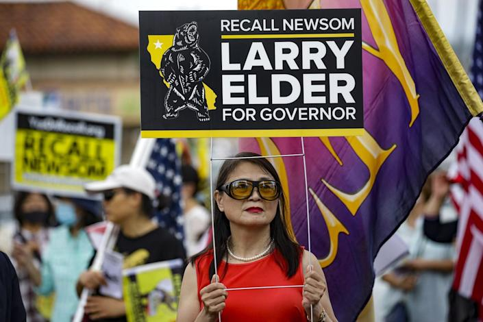 Recall supporters hold signs at a rally