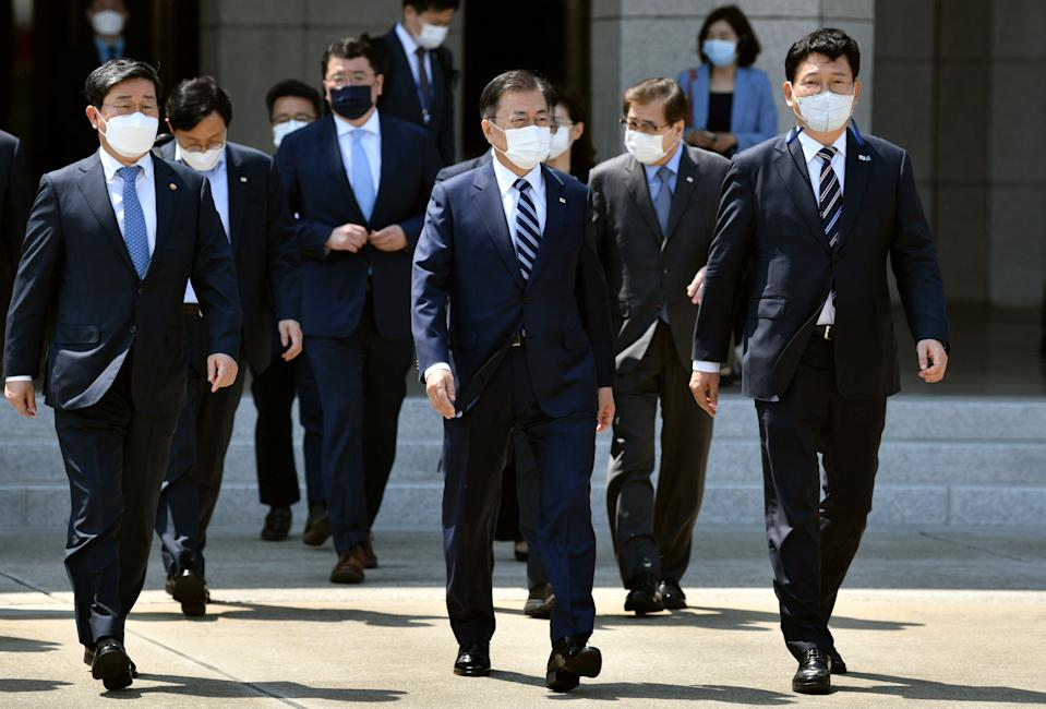 South Korean President Moon Jae-in (C) walks with officials as he leaves for the United States at Seoul Air Base in Seongnam, south of Seoul, on May 19, 2021. (Photo by Jung Yeon-je / AFP) (Photo by JUNG YEON-JE/AFP via Getty Images)