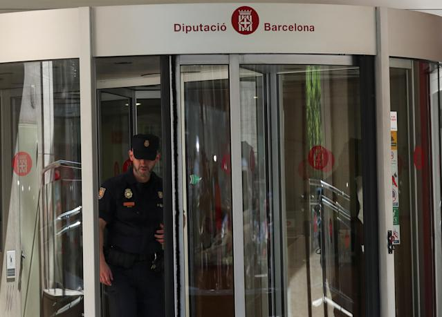A Spanish national police officer exits one of the Catalan public offices which were raided as police investigators raided several Catalan public institutions in search of evidence of alleged rerouting of public funds to organisations associated with a pro-independence bid, according to Spanish media, in Barcelona, Spain, May 24, 2018. REUTERS/Albert Gea