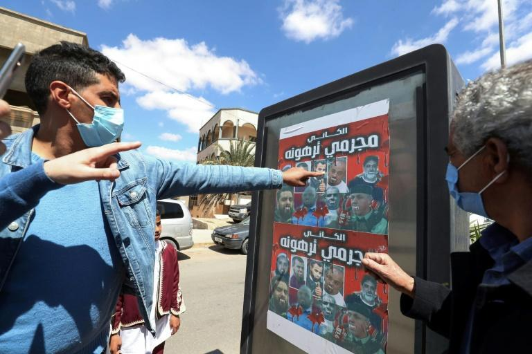 Libyans look at a poster depicting members of the family that commanded a militia that traumatised Tarhuna town